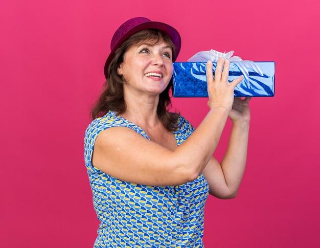 Mulher de meia-idade com chapéu de festa segurando um presente, feliz e alegre, sorrindo amplamente