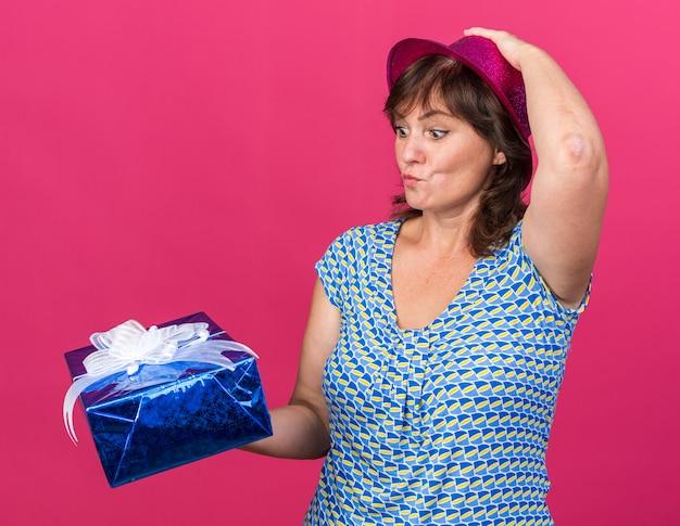 Mulher de meia-idade com chapéu de festa segurando um presente, olhando para ele, confuso com a mão na cabeça, comemorando a festa de aniversário em pé sobre a parede rosa