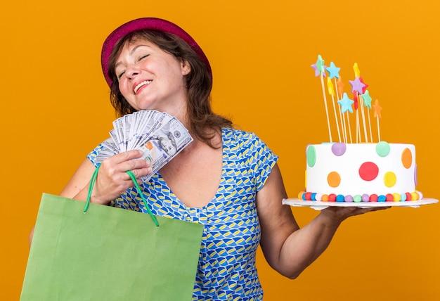 Mulher de meia-idade com chapéu de festa segurando um saco de papel com presentes segurando um bolo de aniversário e dinheiro feliz e satisfeita sorrindo alegremente