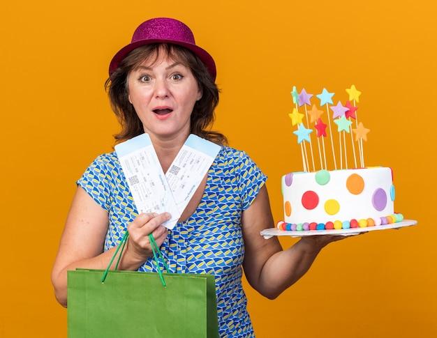 Mulher de meia-idade com chapéu de festa segurando um saco de papel com presentes segurando um bolo de aniversário e passagens aéreas feliz e surpresa