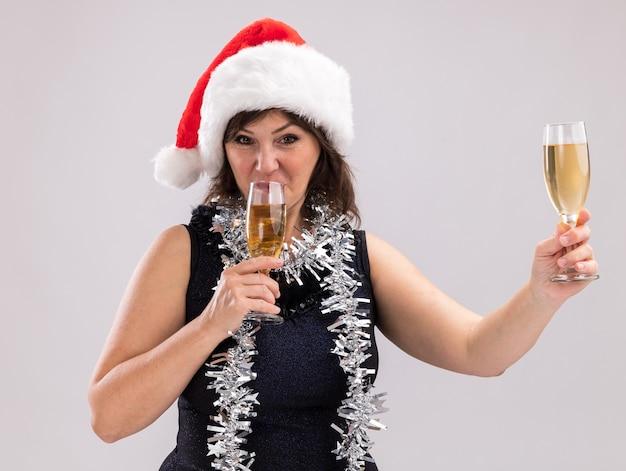 Mulher de meia-idade com chapéu de papai noel e guirlanda de ouropel no pescoço segurando duas taças de champanhe, bebendo uma delas esticando a outra, olhando para a câmera