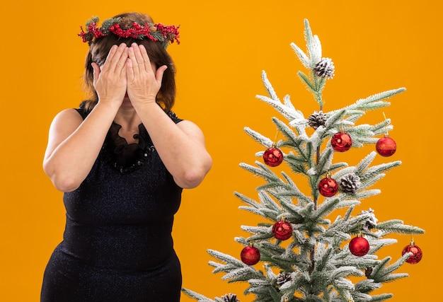 Mulher de meia-idade com coroa de natal na cabeça e guirlanda de ouropel no pescoço, em pé perto da árvore de natal decorada, cobrindo o rosto com as mãos isoladas na parede laranja