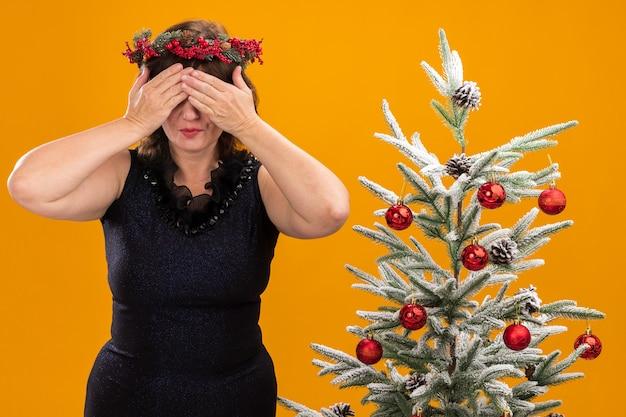 Mulher de meia-idade com coroa de natal na cabeça e guirlanda de ouropel no pescoço em pé perto da árvore de natal decorada