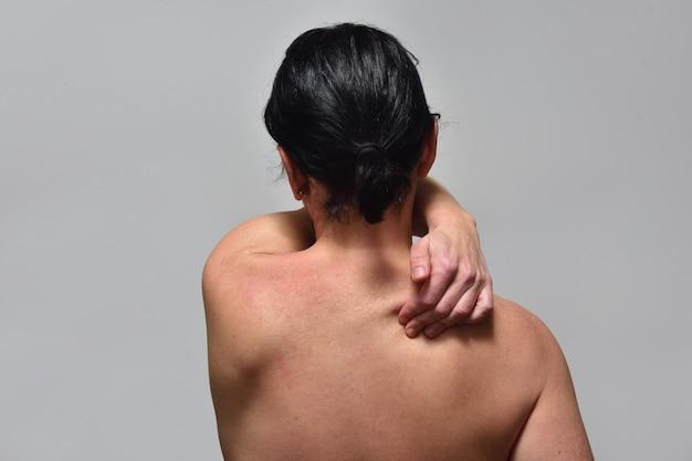 Mulher de meia idade com dor na parte superior da coluna vertebral