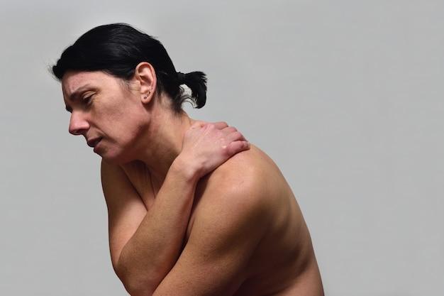 Mulher de meia idade com dor no ombro