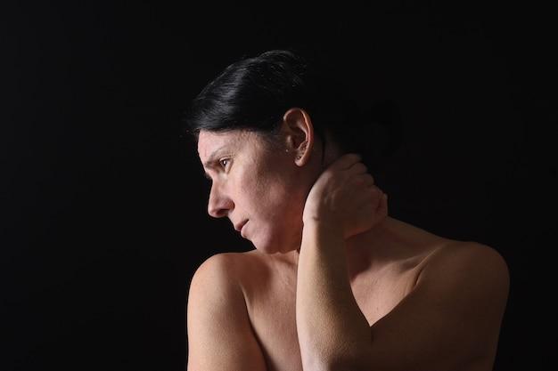 Mulher de meia idade com dor no pescoço em fundo preto