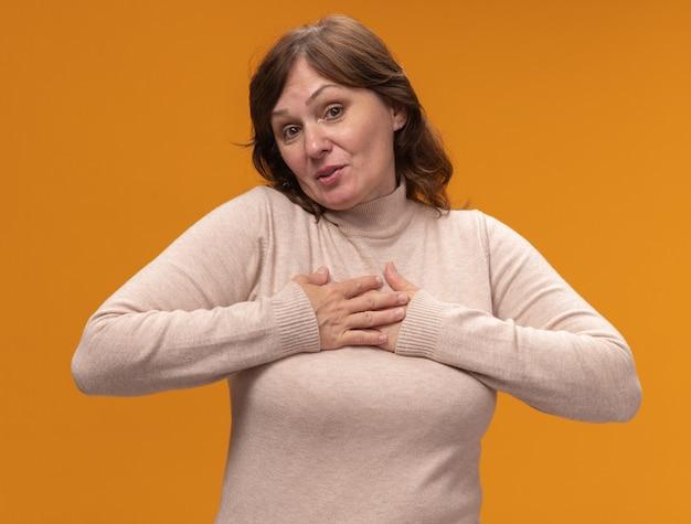 Mulher de meia-idade com gola alta bege de mãos dadas no peito e sentindo-se grata em pé sobre a parede laranja