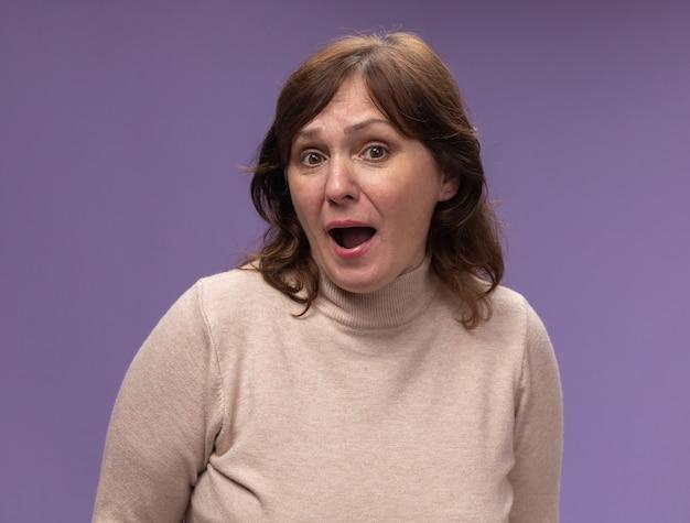 Mulher de meia-idade com gola alta bege preocupada e assustada em pé sobre a parede roxa