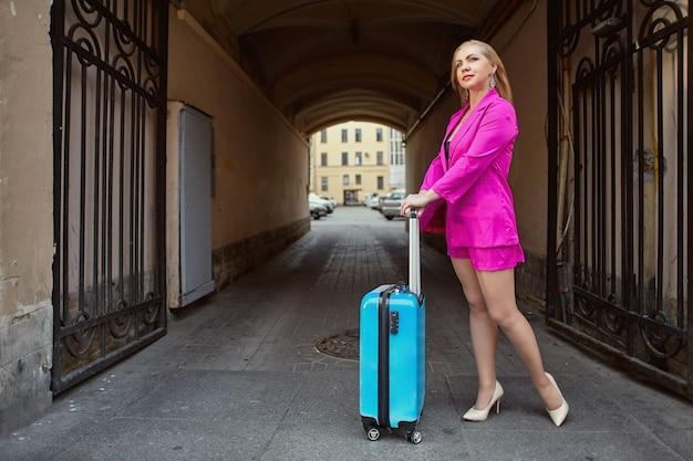 Mulher de meia-idade com mala de viagem esperando um táxi perto de casa