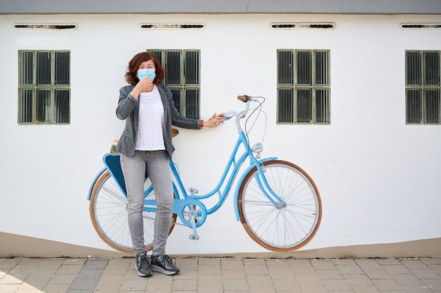 Mulher de meia-idade com máscara facial encostada na parede com bicicleta pintada
