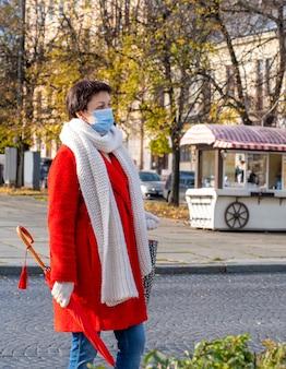 Mulher de meia-idade com máscara médica protetora no rosto caminha na rua na cidade durante o período covid-19
