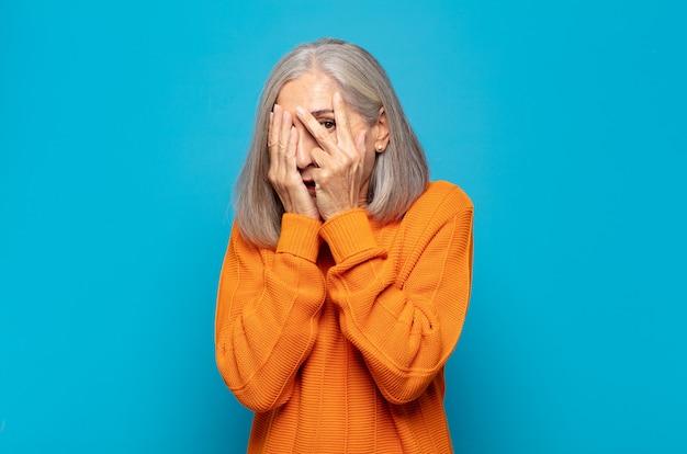 Mulher de meia-idade com medo ou vergonha de espiar ou espiar com os olhos semicerrados pelas mãos