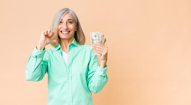 Mulher de meia-idade com notas de dólar na parede da cópia