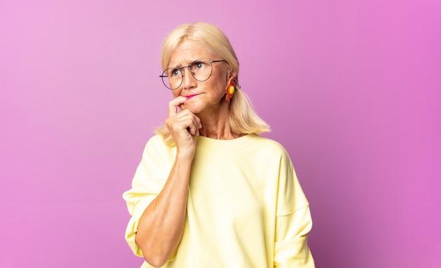 Mulher de meia idade com olhar surpreso, nervoso, preocupado ou amedrontado, olhando para o lado em direção ao espaço da cópia