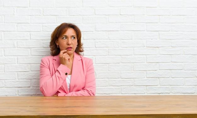 Mulher de meia idade com olhar surpreso, nervoso, preocupado ou assustado, olhando para o lado em direção ao espaço da cópia