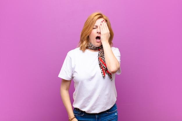 Mulher de meia idade com sono, entediada e bocejando, com dor de cabeça e uma mão cobrindo metade do rosto