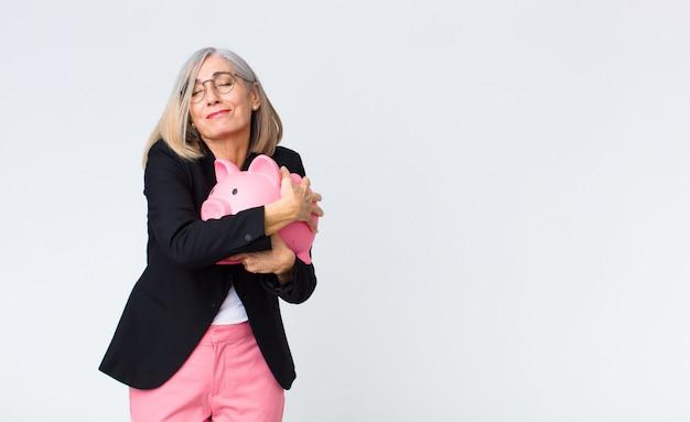 Mulher de meia idade com um cofrinho. conceito de poupança
