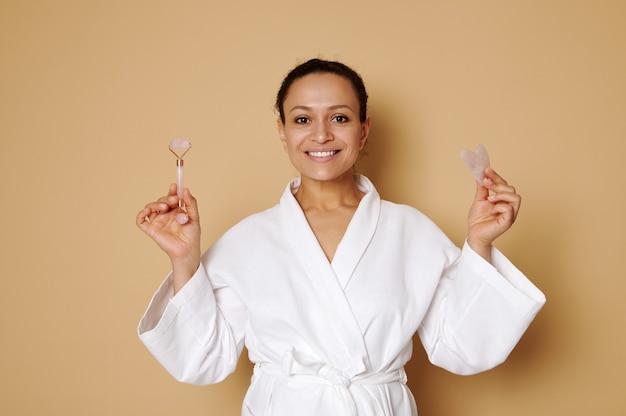 Mulher de meia-idade com um lindo sorriso em um roupão de waffle branco posando com gua sha e massageador de rolo de jade em suas mãos isoladas sobre uma superfície bege com espaço de cópia