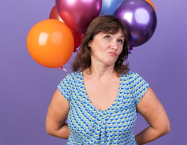 Mulher de meia-idade com um monte de balões coloridos olhando confusa
