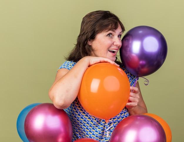 Mulher de meia-idade com um monte de balões coloridos olhando para o lado com um sorriso no rosto feliz