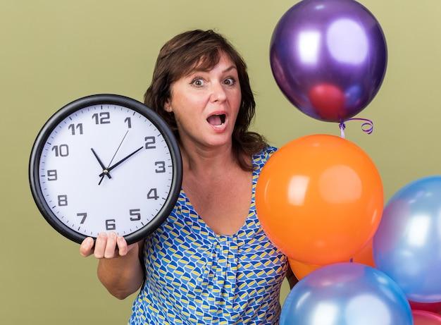 Mulher de meia-idade com um monte de balões coloridos segurando um relógio de parede espantada e surpresa