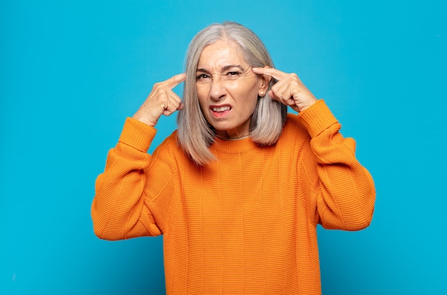 Mulher de meia idade com um olhar sério e concentrado, fazendo um brainstorming e pensando sobre um problema desafiador