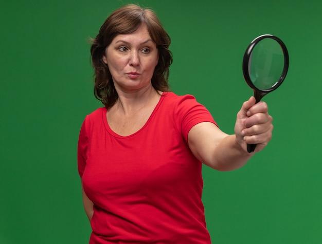 Mulher de meia-idade com uma camiseta vermelha segurando uma lupa e olhando para ela com uma cara séria em pé sobre uma parede verde