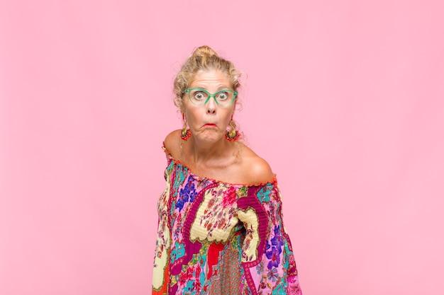 Mulher de meia idade com uma expressão boba, louca e surpresa, bochechas estufadas, sentindo-se recheada, gorda e cheia de comida