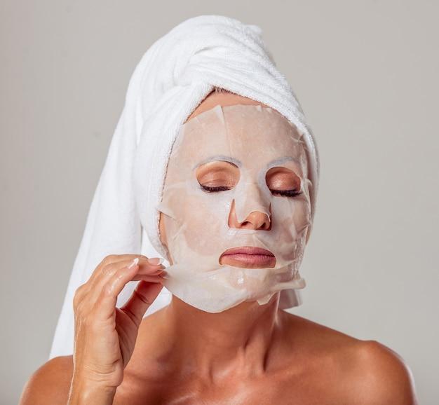 Mulher de meia idade com uma toalha na cabeça
