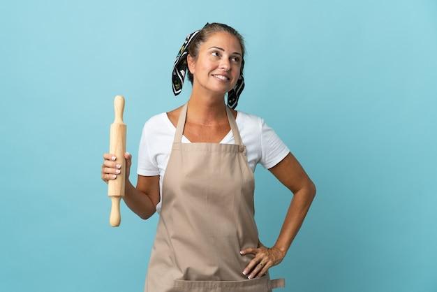 Mulher de meia-idade com uniforme de chef pensando em uma ideia enquanto olha para cima