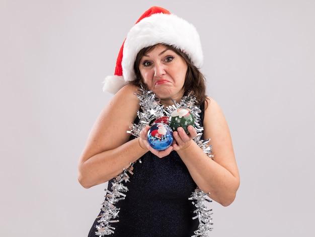Mulher de meia-idade confusa com chapéu de papai noel e guirlanda de ouropel no pescoço segurando enfeites de natal, olhando para a câmera isolada no fundo branco com espaço de cópia