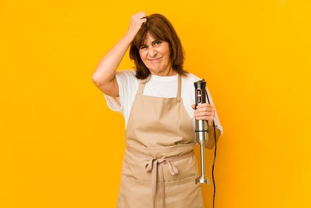 Mulher de meia-idade, cozinheira, caucasiana, segurando uma batedeira isolada e ficando em choque