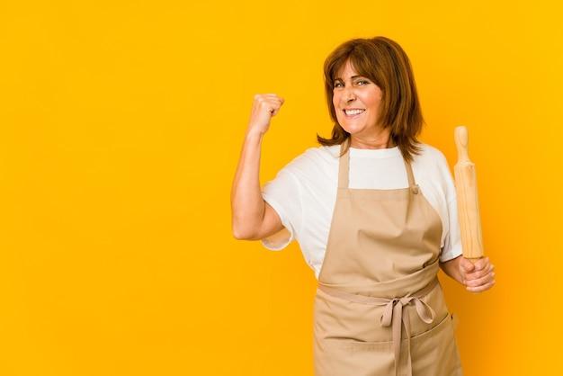 Mulher de meia-idade, cozinheiro, caucasiano, segurando um rolo isolado levantando o punho após uma vitória, o conceito de vencedor.