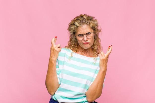 Mulher de meia-idade cruzando os dedos ansiosamente e esperando boa sorte com um olhar preocupado