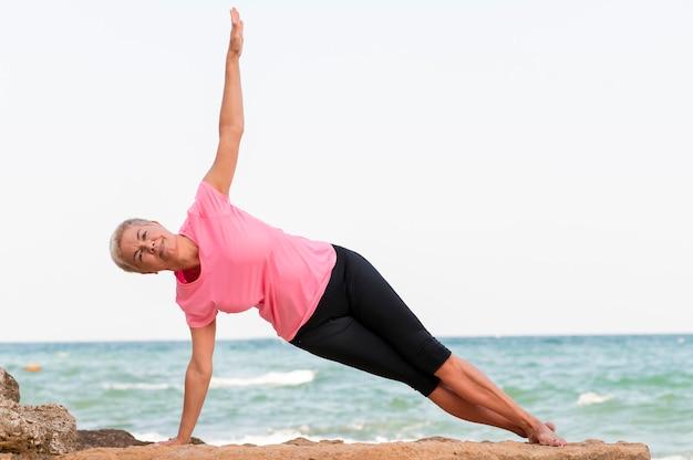 Mulher de meia idade da vista lateral fazendo pilates na praia. foto de alta qualidade