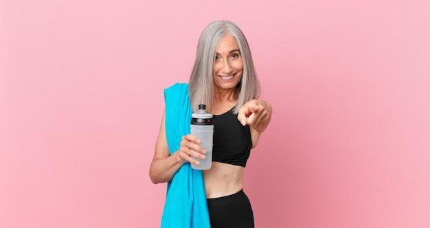 Mulher de meia-idade de cabelo branco apontando para a câmera escolhendo você com uma toalha e uma garrafa de água. conceito de fitness
