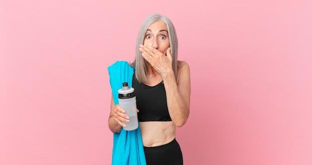 Mulher de meia-idade de cabelo branco cobrindo a boca com as mãos com uma toalha chocada e uma garrafa de água. conceito de fitness