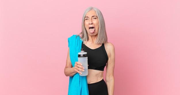 Mulher de meia-idade de cabelo branco com atitude alegre e rebelde, brincando e mostrando a língua com uma toalha e uma garrafa de água. conceito de fitness