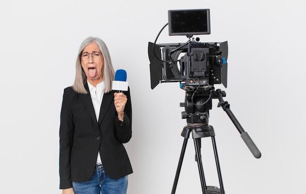 Mulher de meia-idade de cabelo branco com atitude alegre e rebelde, brincando e mostrando a língua e segurando um microfone. conceito de apresentador de televisão
