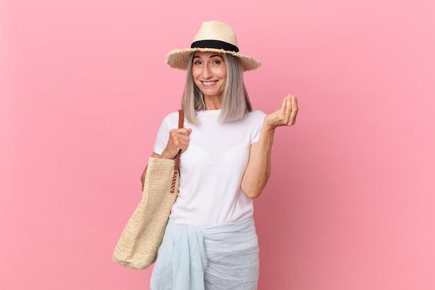 Mulher de meia-idade de cabelo branco fazendo capice ou gesto de dinheiro, dizendo para você pagar. conceito de verão