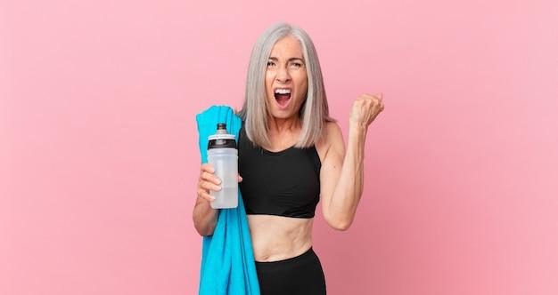 Mulher de meia-idade de cabelo branco gritando agressivamente com uma expressão de raiva com uma toalha e uma garrafa de água. conceito de fitness