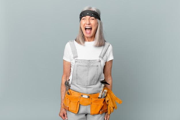Mulher de meia-idade de cabelo branco gritando agressivamente, parecendo muito zangada e usando roupas de trabalho e ferramentas. conceito de limpeza