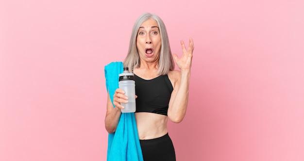 Mulher de meia-idade de cabelo branco gritando com as mãos no ar com uma toalha e uma garrafa de água. conceito de fitness