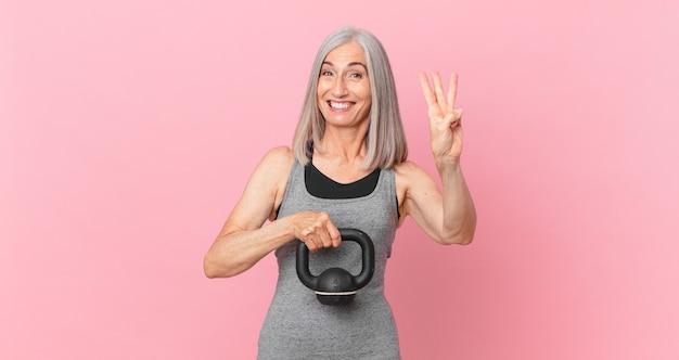 Mulher de meia-idade de cabelo branco levantando um haltere. conceito de fitness