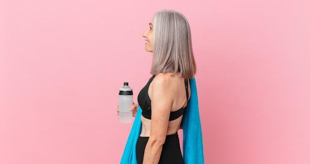 Mulher de meia-idade de cabelo branco na vista de perfil, pensando, imaginando ou sonhando acordada com uma toalha e uma garrafa de água. conceito de fitness