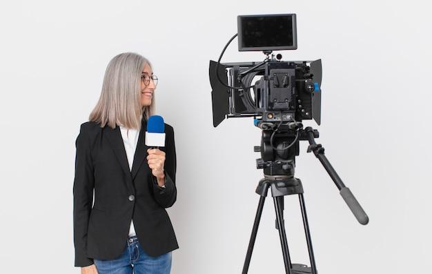 Mulher de meia-idade de cabelo branco na vista de perfil, pensando, imaginando ou sonhando acordada e segurando um microfone. conceito de apresentador de televisão