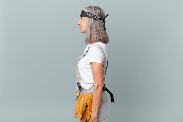 Mulher de meia-idade de cabelo branco na vista de perfil, pensando, imaginando ou sonhando acordada e usando roupas de trabalho e ferramentas. conceito de limpeza