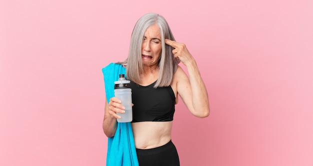 Mulher de meia-idade de cabelo branco olhando infeliz e estressada, gesto de suicídio fazendo sinal de arma com uma toalha e uma garrafa de água. conceito de fitness