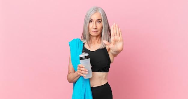 Mulher de meia-idade de cabelo branco olhando sério, mostrando a palma da mão aberta, fazendo gesto de parada com uma toalha e uma garrafa de água. conceito de fitness