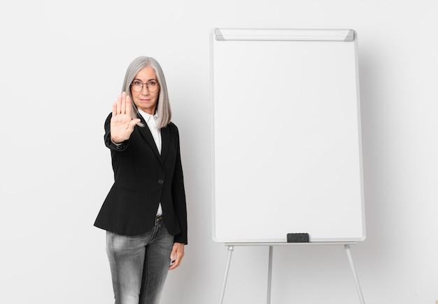 Mulher de meia-idade de cabelo branco olhando sério, mostrando a palma da mão aberta, fazendo o gesto de parada e um espaço de cópia de placa. conceito de negócios